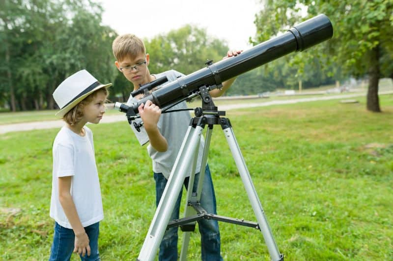 2 Boys Setting Up A Kids Telescope